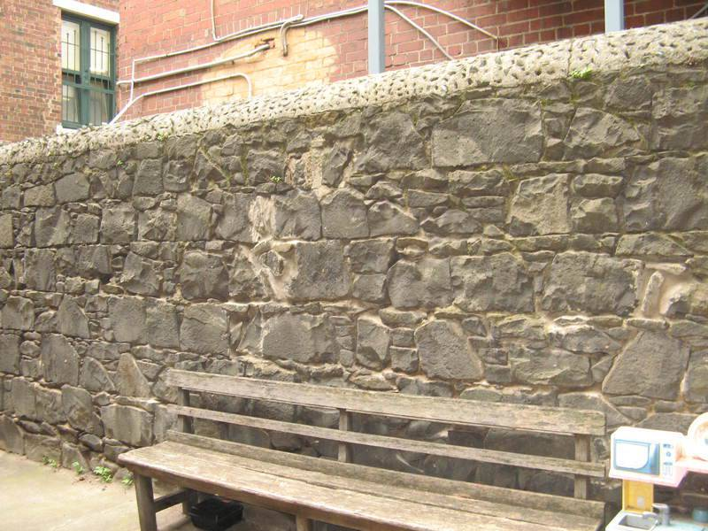 Basalt wall of coursed rubble, west boundary