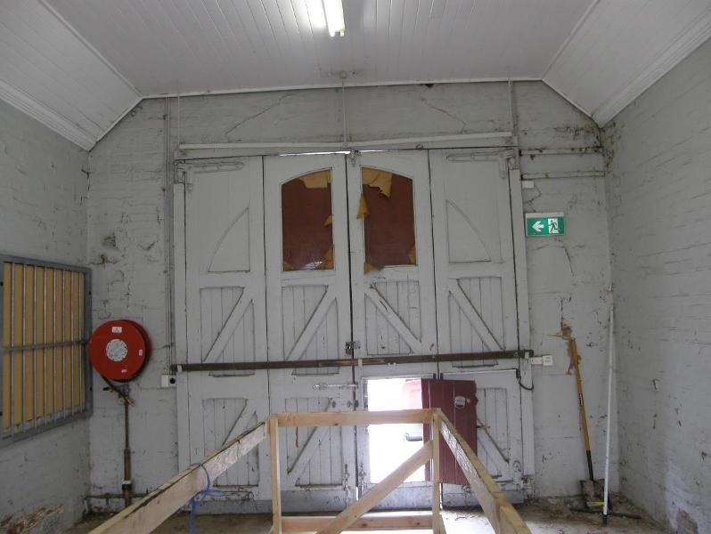 Looking west at the timber and glass doors to the former fire engine room
