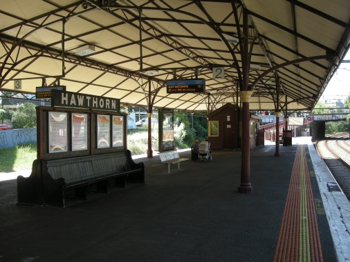 Looking north from the mid-point of the edge of Platform 2 - the Station nameboard and back-to-back timber benches in foreground are significant elements