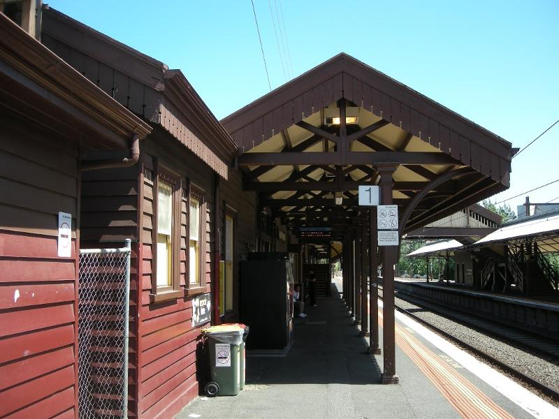 Looking southward along Platform 1 at its buildings and canopy - the canopy timber king-post trusses and support brackets of bent rail are visible