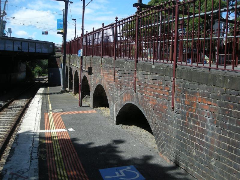 Looking north along Platform 3 at the west-facing brick wall beneath the walkway